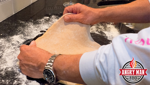 This crust should stretch out easily once you have flattened it a bit by pressing. Use flour to keep the dough from sticking to you work surface.